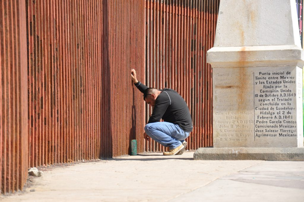 Man says goodbye to his partner through the US-Mexico border fence.