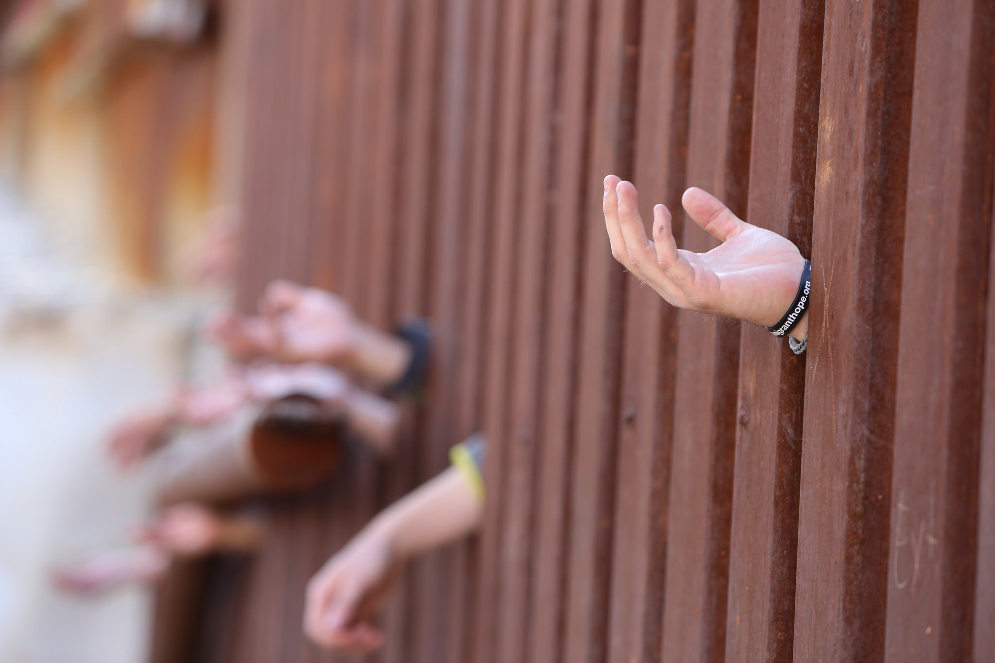 Hands reach across fence of US-Mexico border