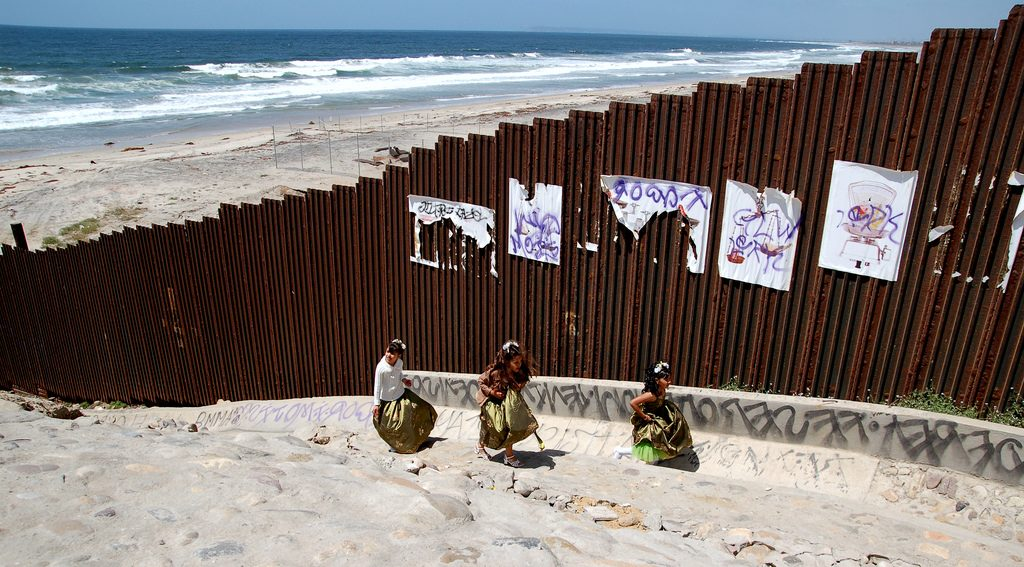 Girls playing on a beach in TIjuana near the US-Mexico border fence.