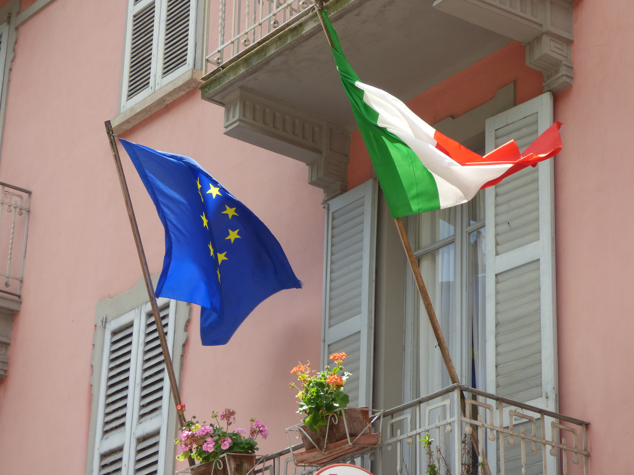 Flags of the European Union and Italy fly side-by-side